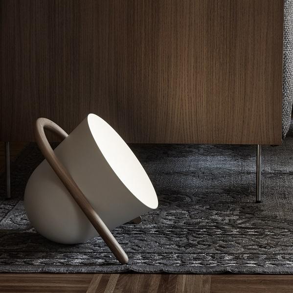 INCIPIT ELMA vloerlamp wit. Elma is een vloerlamp die indirect licht verspreidt en bestaat uit twee hoofdelementen die verschillen in materiaal en vorm: de aluminium kap die de lichtbron/lamp bevat en een gebogen eikenhouten handvat+voet.